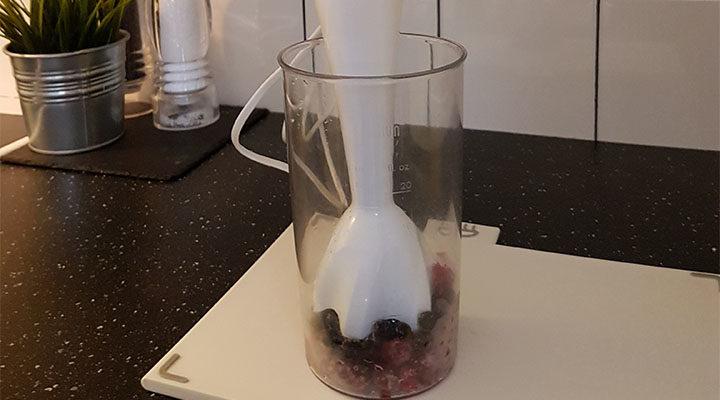 En stavmixer i ett glas med bär