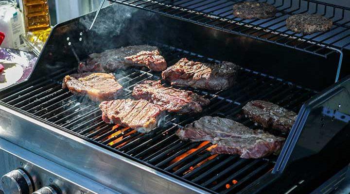 Flera köttbitar som ligger på en gasolgrill