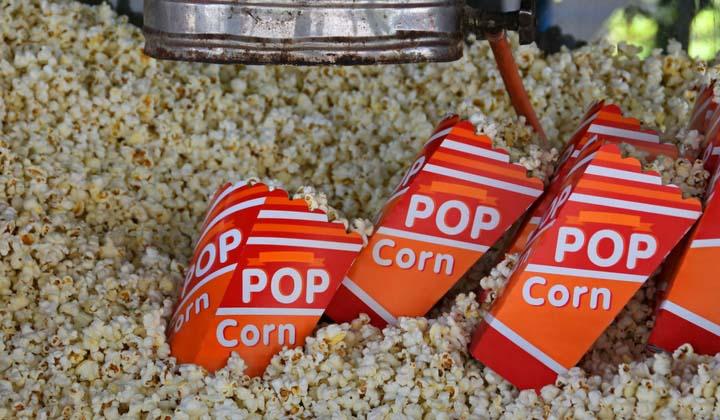 Insidan av en stor popcornmaskin med popcorn och popcornlådor i.