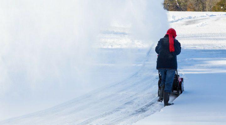 Kvinna som använder en snöslunga.