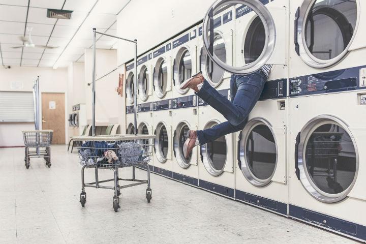 Tvättstuga fylld med tvättmaskiner där en person hänger i en av tvättmaskinerna med halva kroppen inne i samma trättmaskin.