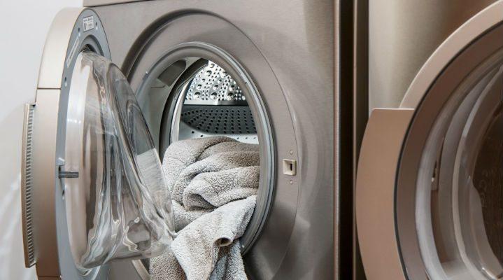 En tvättmaskin med öppen dörr som det ligger en handduk i.