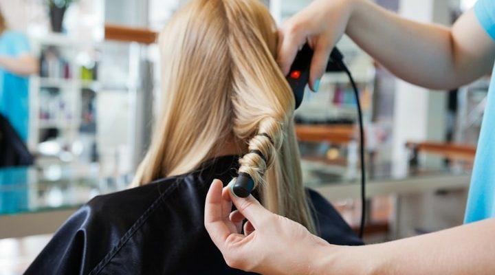 Blondhårig kvinna får sitt hår lockat med locktång.