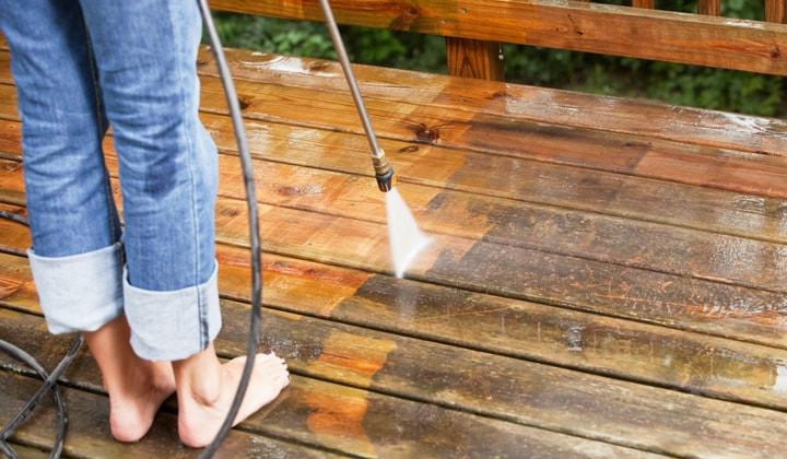 Person står och tvättar altanen med högtryckstvätt.