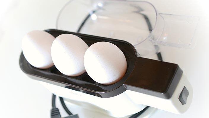 En äggkokare med tre ägg i.