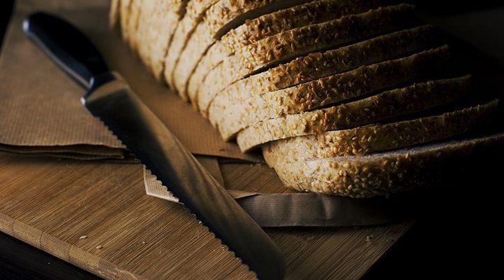 En brödkniv som ligger på en skärbräda där det också ligger bröd som har skurits i skivor.