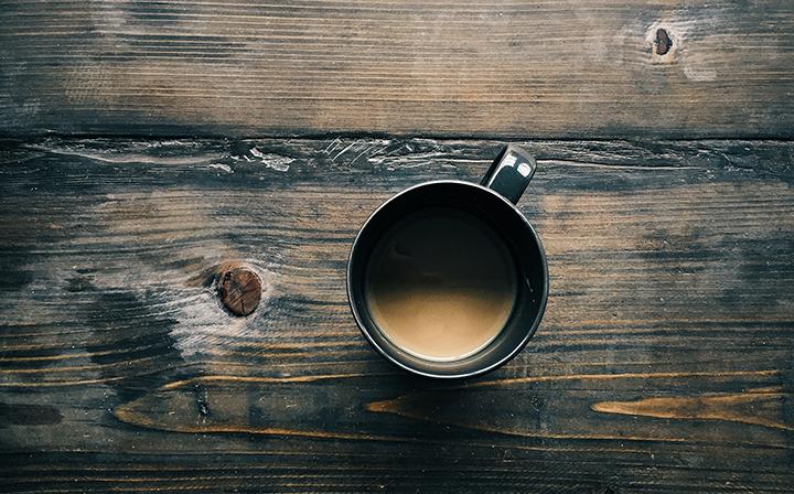 En kopp kaffe på ett träbord.