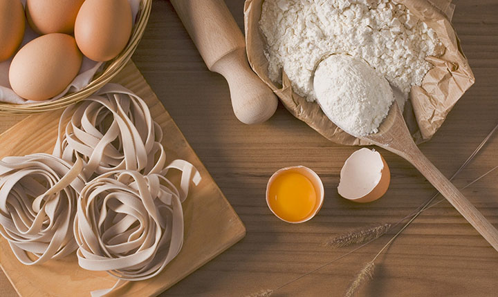 Ingredienser till pasta och tagliatelle som ligger på ett bord.