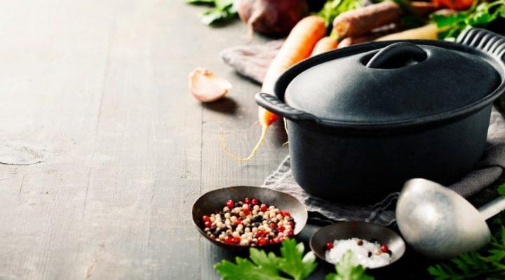 En gjutjärnsgryta som står på ett bord med lite grönsaker och andra prylar.