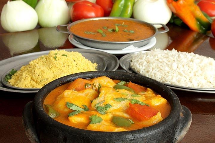 En gryta med lite kyckling, två fat med ris och en gryta med en soppa i.