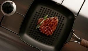 En grillpanna med en köttbit i.
