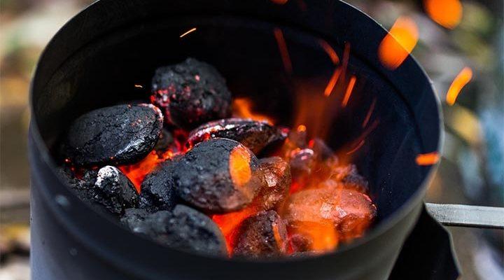 En grilltändare som är i full fart och gläder upp kolen.