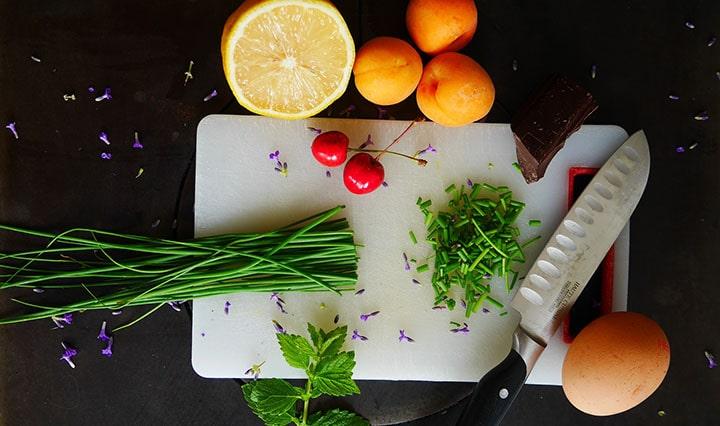 En skärbräda med grönsaker och en grönsakskniv.