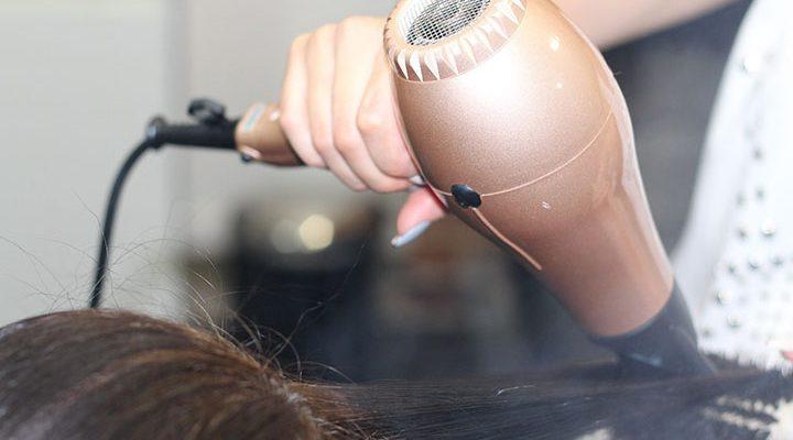 Närbild på brunt hår som blir fönat med hårfön.