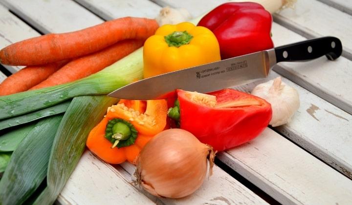 Japansk kniv som skär genom grönsaker.