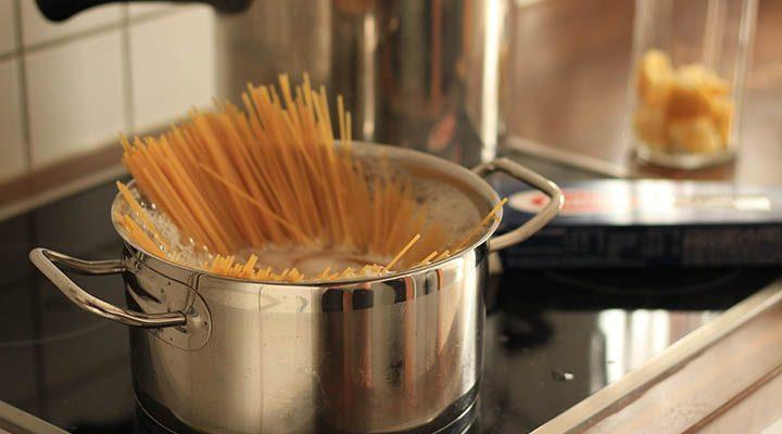 En kastrull på en induktionsspis med spagetti i.