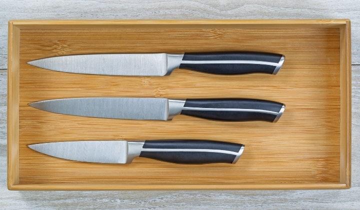 En trälåda med tre stycken knivar i.