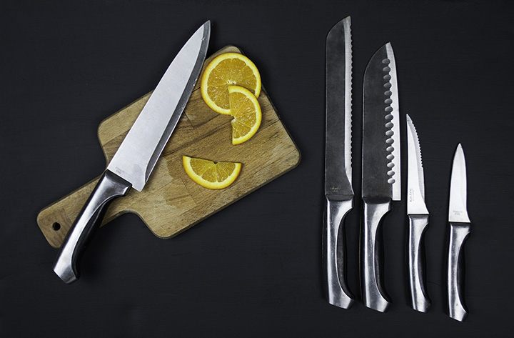 Ett knivset som ligger på ett bord vid en skärbräda.