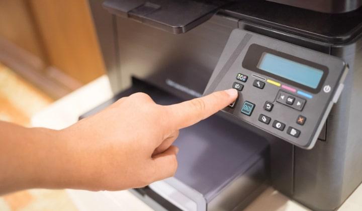 En närbild på en laserskrivare, en person trycker på en knapp.