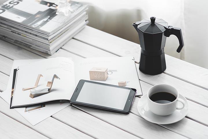 En mokabryggare, massa tidningar, en kaffekopp och en surfplatta på ett bord.