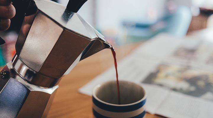 En mokabryggare som häller upp kaffe i en mugg.