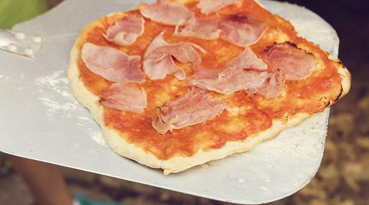 En gräddad pizza på en pizzasten.