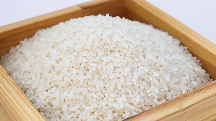 En träskål med vitt ris i.