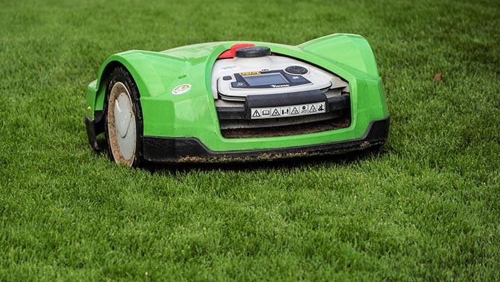 En grön robotgräsklippare som klipper en gräsmatta.