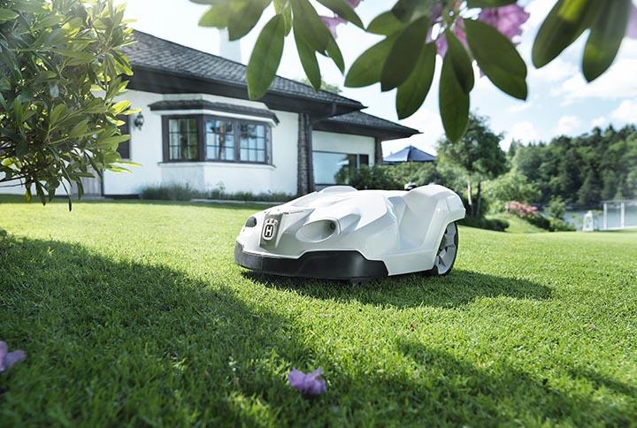 En robotgräsklippare med ett vitt hus i bakgrunden.