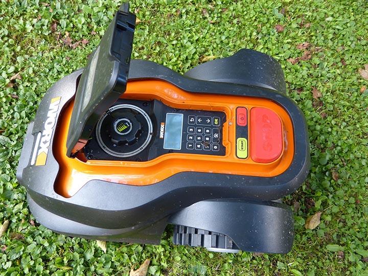 En robotgräsklippare med öppet locka så man ser knappsatsen.