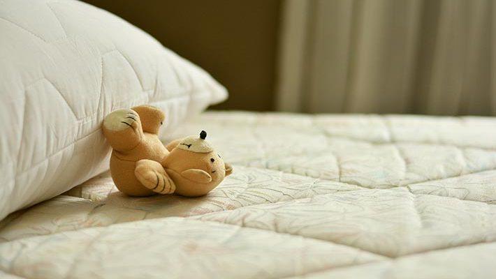 En liten nallebjörn som ligger på en säng.