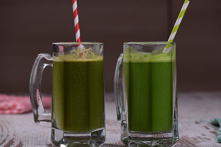 Två glas med grön juice i.