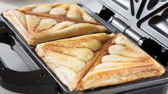 Smörgåsgrill som har två färdiga mackor som precis grillats.