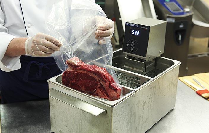 En kock som lägger ner en vakuumförpackad i en sous vide-maskin.