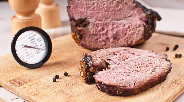 Uppskuret kött på en skärbräda med en stektermometer.