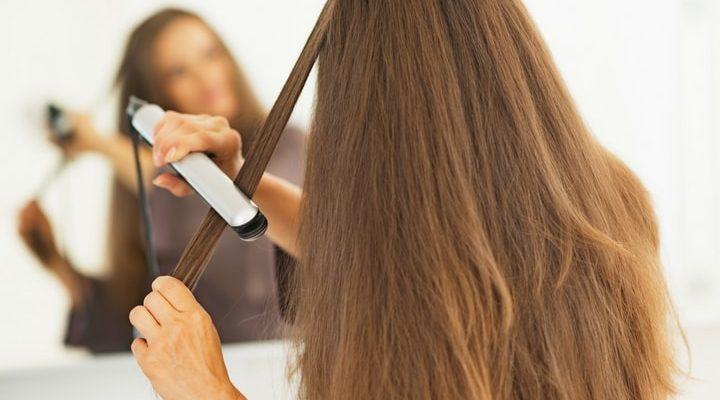 En tjej med brunt, lång hår plattar sitt hår med en plattång.