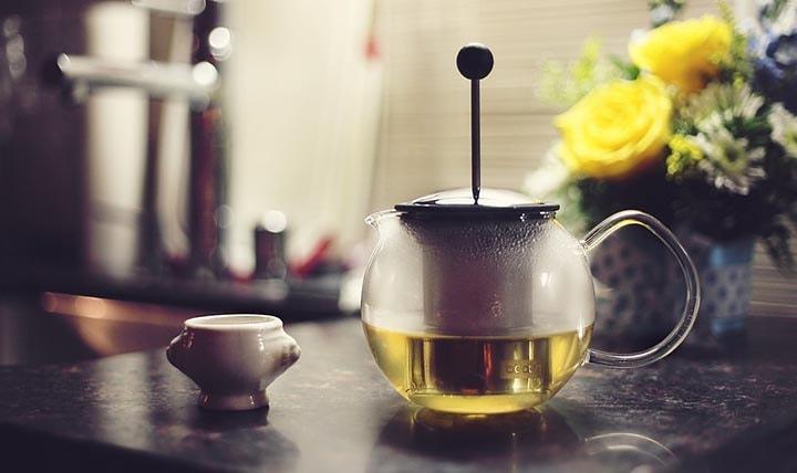 Färdigkokat te i en tekanna bredvid en kopp.