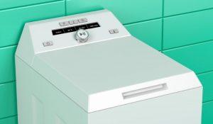 En toppmatad tvättmaskin som står i ett badrum med turkost kakel.