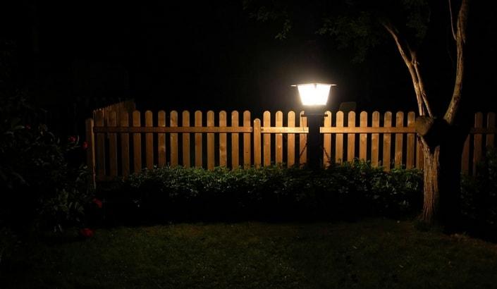 En trädgårdslampa som lyser upp ett staket i mörkret.