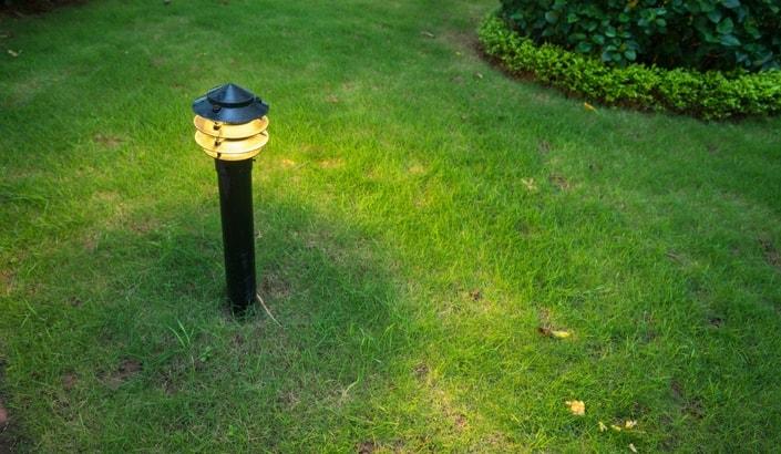 En liten trädgårdslampa som står mitt på en gräsmatta.