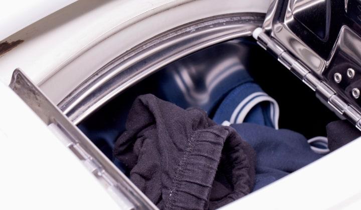 En närbild på toppen av en toppmatad tvättmaskin med kläder i.